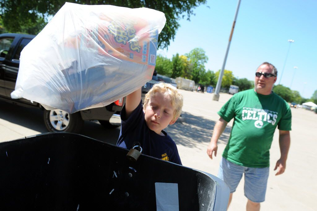 Sam Dee, 7, from Rowlett, throws away paper products while his father, Kenny, watches on during a two-day recycling collection event to celebrate Earth Day in 2012.