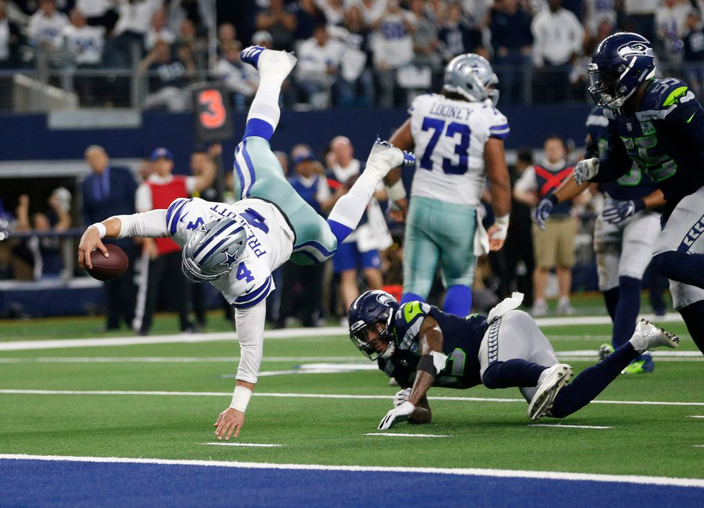 Dallas Cowboys quarterback Dak Prescott (4) dives for more yards but is stopped by Seattle Seahawks free safety Tedric Thompson (33) on a third down play during the second half of play at AT&T Stadium in Arlington, on Saturday, January 5, 2019. The Dallas Cowboys defeated the Seattle Seahawks 24-22 to advance to the next round. (Vernon Bryant/The Dallas Morning News)