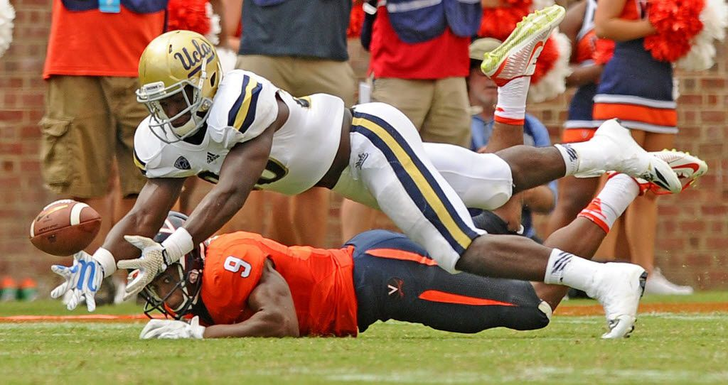 UCLA linebacker Myles Jack almost comes up with an interception in front of Virginia receiver Canaan Severin at Scott Stadium in Charlottsville, Va., on Saturday, Aug. 30, 2014. UCLA won, 28-20. (Wally Skalij/Los Angeles Times/MCT) 09122014xSPORTS