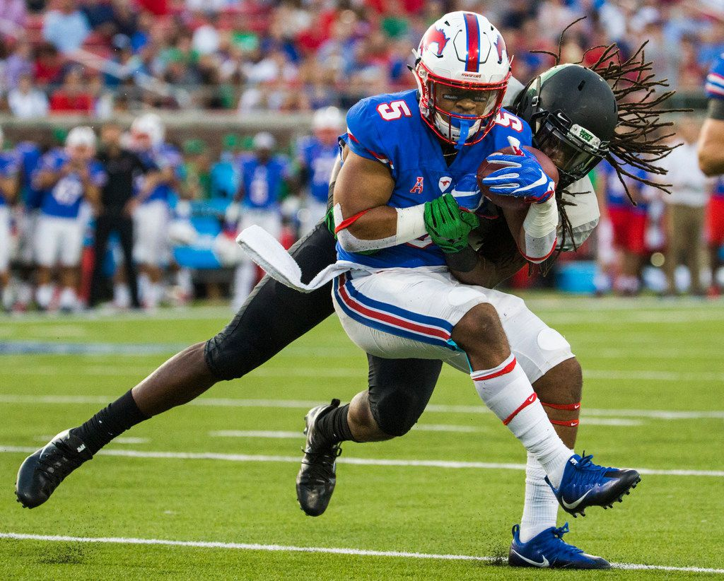 SMU running back Xavier Jones (5) is tackled by North Texas linebacker Joshua Wheeler (18) during the second quarter of an NCAA college football game Saturday, Sept. 9, 2017, in Dallas. (Ashley Landis/The Dallas Morning News via AP)