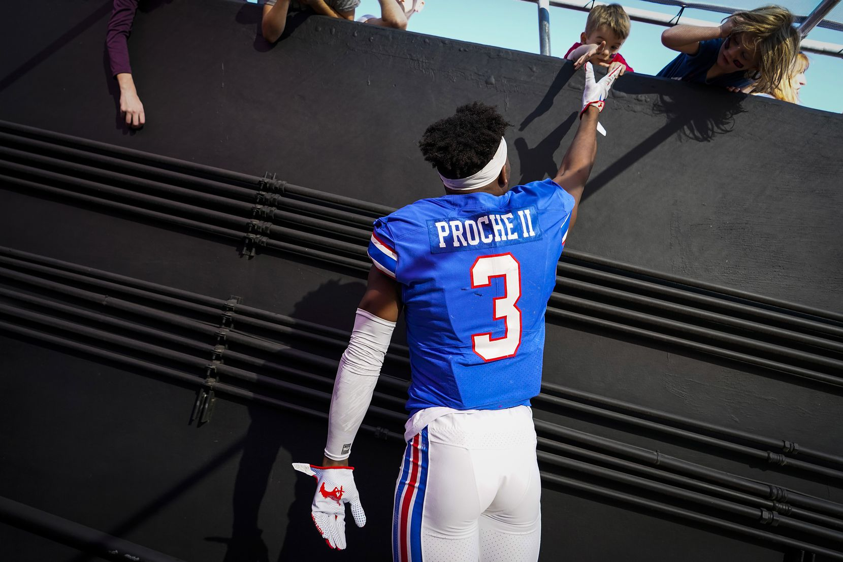 SMU wide receiver James Proche jumps to high five a young fan before an NCAA football game against Tulane at Ford Stadium on Saturday, Nov. 30, 2019, in Dallas.