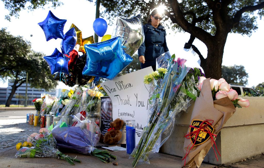 A makeshift memorial honors San Antonio police Officer Benjamin Marconi, 50, a 20-year veteran of the force who was fatally shot Sunday near police headquarters. (Eric Gay/The Associated Press)