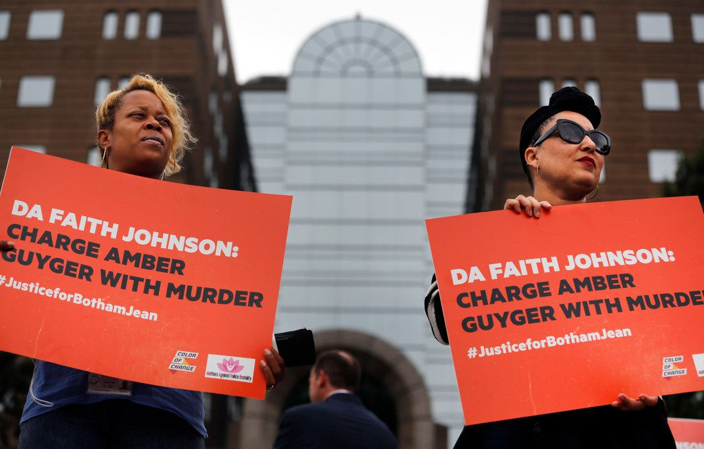 Tiki Fite (left) and Heather Smith both of Dallas support the nonprofit organization Color of Change who held up signs to passing cars on Riverfront Blvd in Dallas, Friday, September 28, 2018.   The group held a rally outside the Frank Crowley Courts Building in Dallas before delivering an estimated 170,000 signatures in a petition urging Dallas County District Attorney Faith Johnson to pursue murder charges against fired Dallas police officer Amber Guyger. Guyger shot and killed Botham Jean in his apartment building earlier in September. (Tom Fox/The Dallas Morning News)