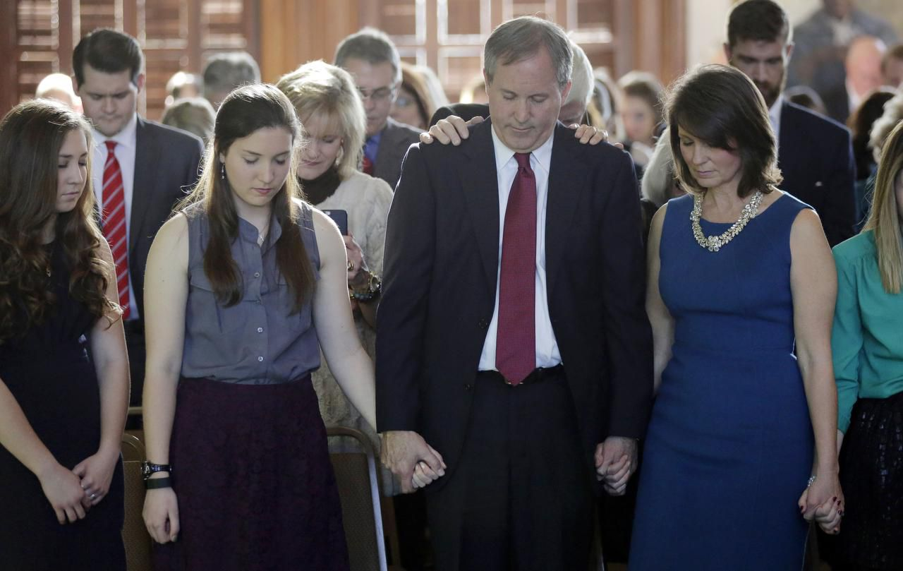 Ken Paxton, center, joins hands with family members during a prayer after he was sworn in as the Texas attorney general, Monday, Jan. 5, 2015, in Austin, Texas. (AP Photo/Eric Gay)