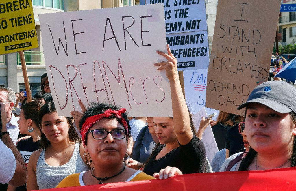 Supporters of the Deferred Action for Childhood Arrivals, or DACA chant slogans and hold signs while joining a Labor Day rally in downtown Los Angeles on Monday.