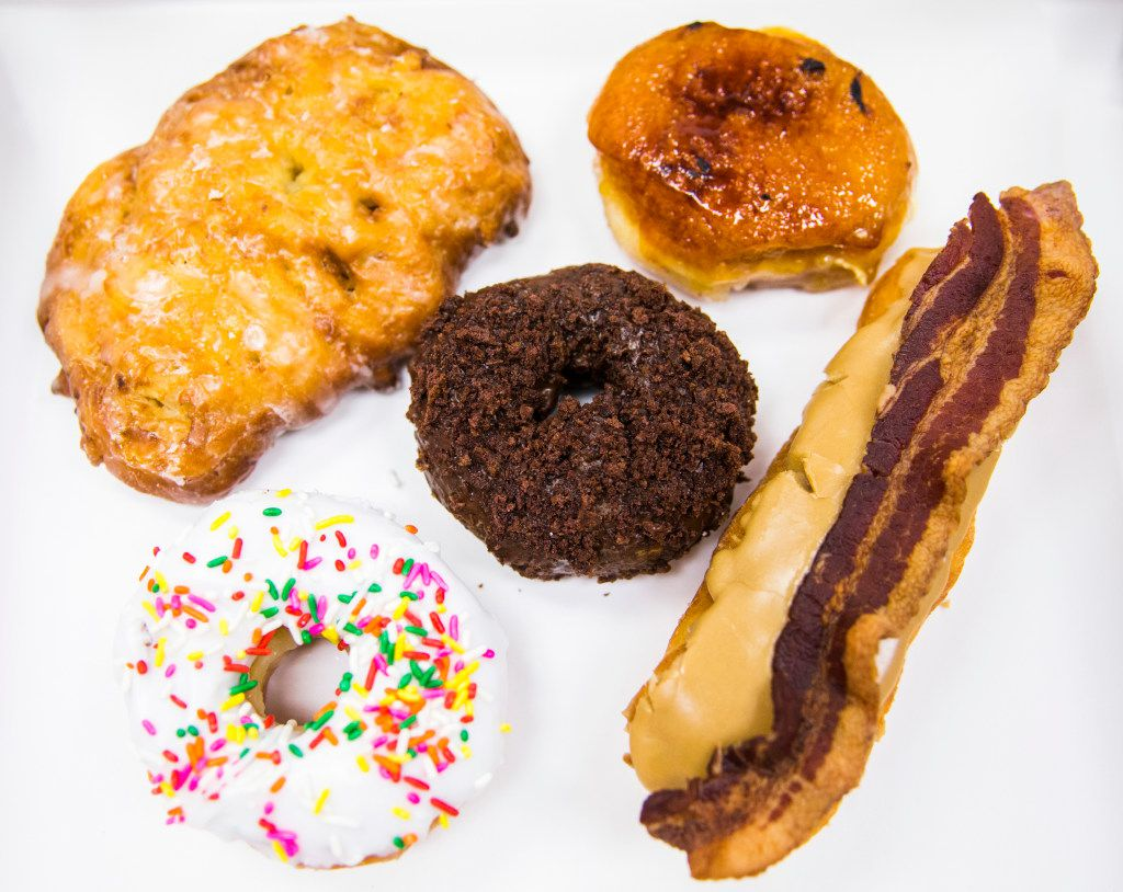 Clockwise, an apple fritter, a creme bržlŽe filled donut, a maple bacon bar, a vanilla sprinkles donut and a chocolate chocolate cake donut, center, on Thursday, March 30, 2017 at Rise Biscuits Donuts in Allen, Texas. (Ashley Landis/The Dallas Morning News)