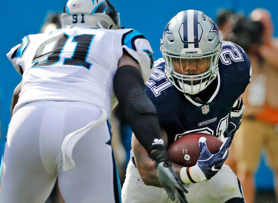 Cowboys running back Ezekiel Elliott (21) looks for an opening as Panthers defensive end Bryan Cox (91) moves in for a tackle during the first quarter of a game at Bank of America Stadium in Charlotte, N.C., on Sunday, Sept. 9, 2018. (Louis DeLuca/The Dallas Morning News)