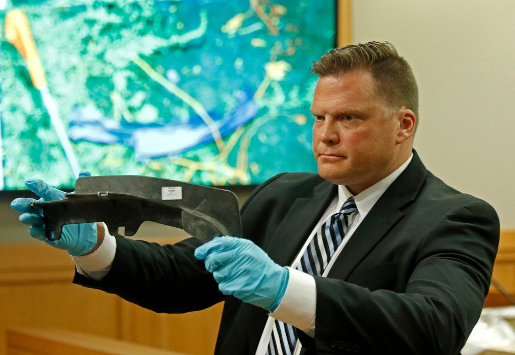 Richardson Detective Eric Willadsen shows the jury an auto part found at the crime scene in Farmersville during the Jason Lowe murder trial at the Collin County Courthouse in McKinney, Texas, on Monday.