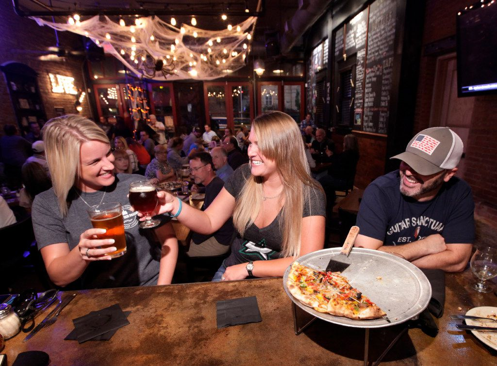 Mindy Bray, left, Cosmo Underwood, and Stace Carpenter enjoy some beer and pizza at Cadillac Pizza Pub in McKinney.