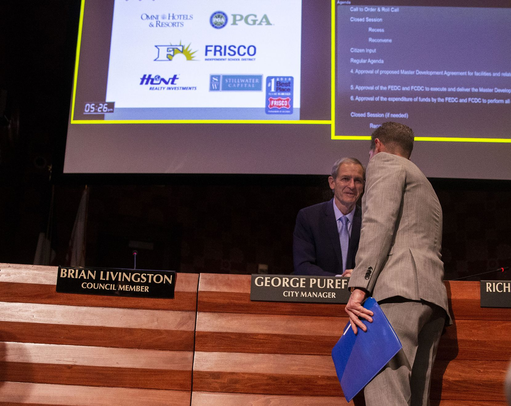 City manager George Purefoy (facing camera) shakes hands with Darrell Crall, PGA of America Chief Operating Officer, after a Frisco City Council meeting at the George A. Purefoy Municipal Center in Frisco, Texas, on Tuesday, December 4, 2018.