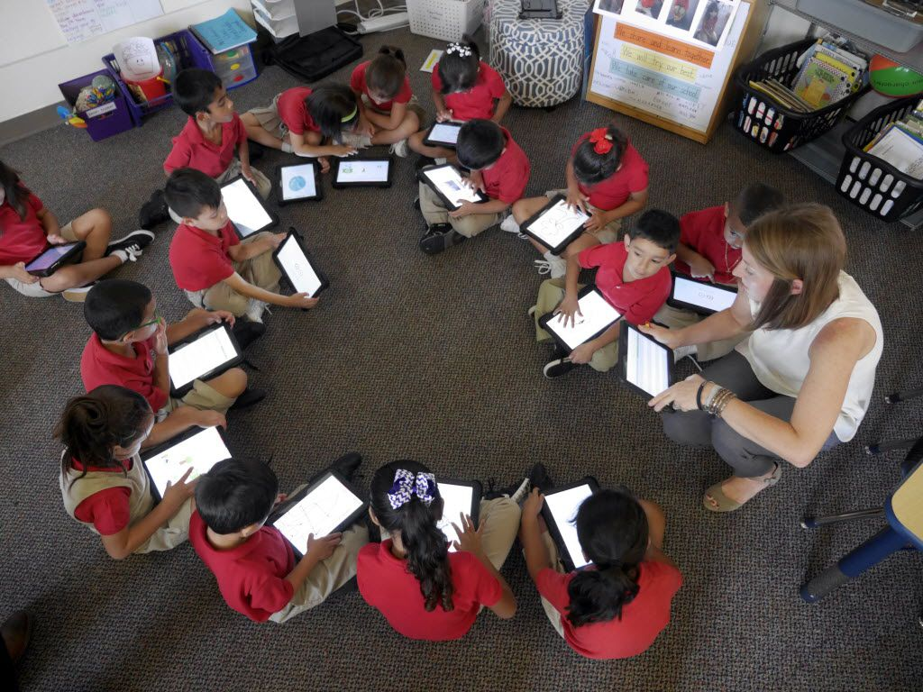 Momentous School of Dallas students form a circle as they do work on tablets.
