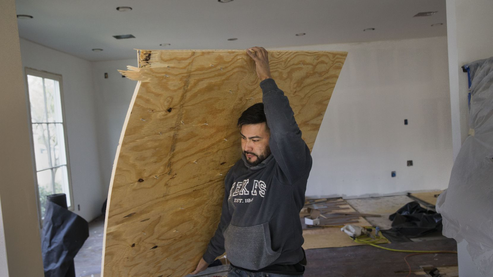 A contractor working for Marvelous Home Makeovers carries plywood at a home being remodeled in University Park.