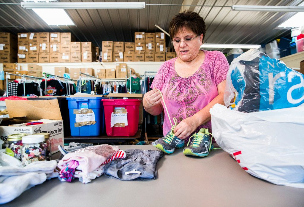 Employee Irma Eilert laces a pair of tennis shoes at Second Chance Emporium on Wednesday, October 11, 2017 in La Grange, Texas. The non-profit store provided clothing and supplies for flood victims for the entire month of September, after losing their own building. Major flooding damaged hundreds of homes in the city due to flooding from Hurricane Harvey. Record amounts of rain caused the Colorado River, which borders La Grange, to raise up about 54 feet. (Ashley Landis/The Dallas Morning News)
