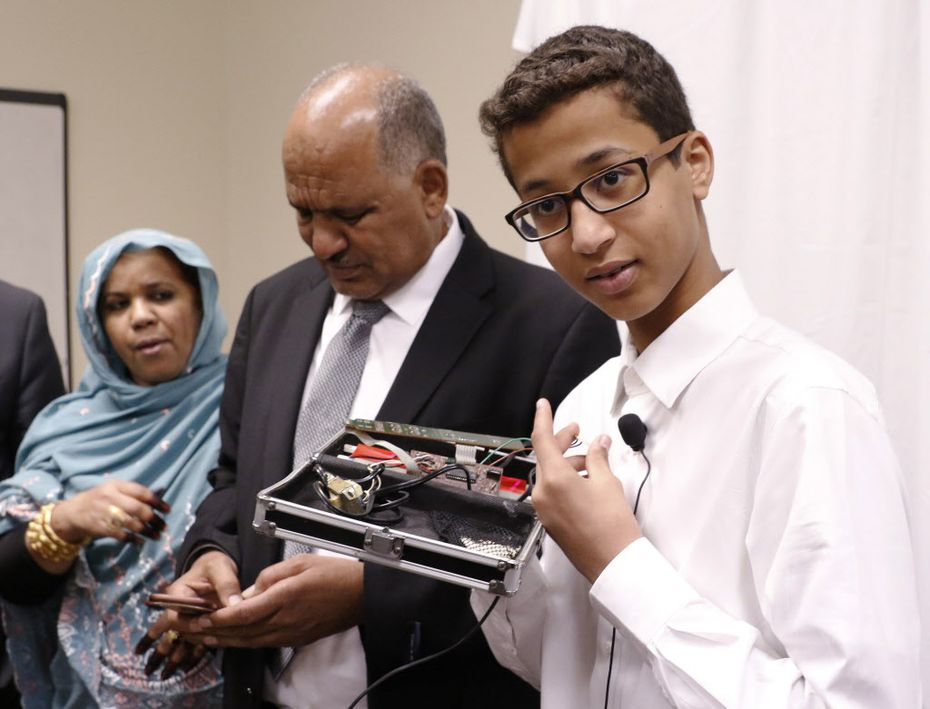 "Ahmed Mohamed, right, labeled ""Clock Boy"" shows the clock he built in a school pencil box while standing with his parents, Muna Ibrahim, left, and Mohamed Elhassan, after a news conference in Dallas, Monday, August 8, 2016."