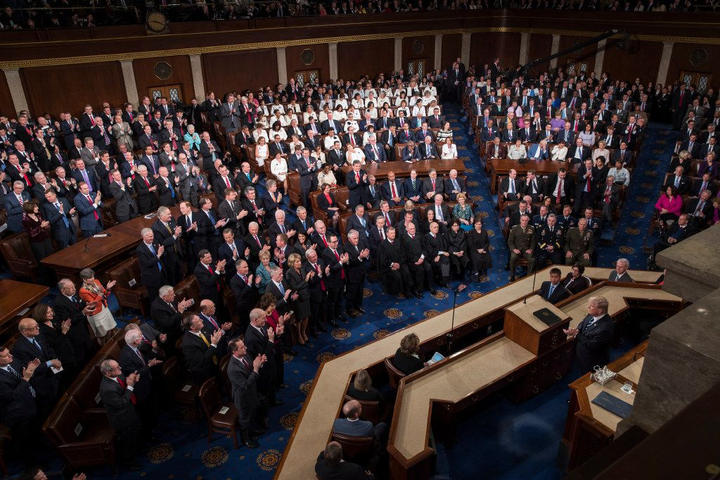 Republicans applaud at left as most Democrats remain seated as President Donald Trump addresses a joint session of Congress on Capitol Hill in Washington, Feb. 28, 2017. (Stephen Crowley/The New York Times)