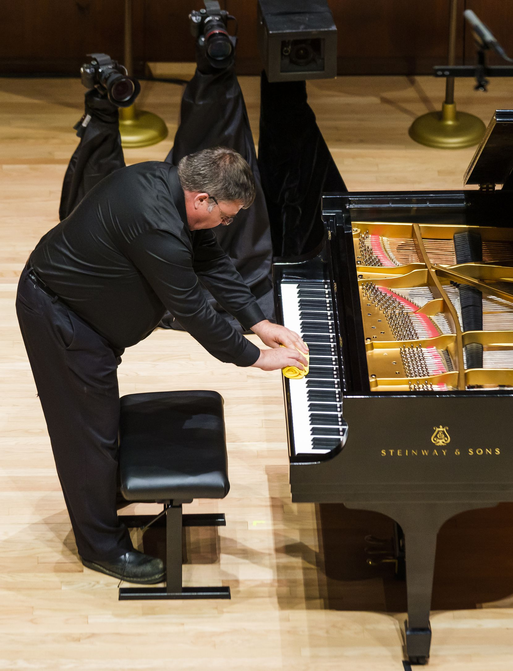 Michael McNicholas wipes off the keys of the piano between performances during the quarterfinals of The Cliburn Junior International Piano Competition at SMU's Caruth Auditorium in 2019.