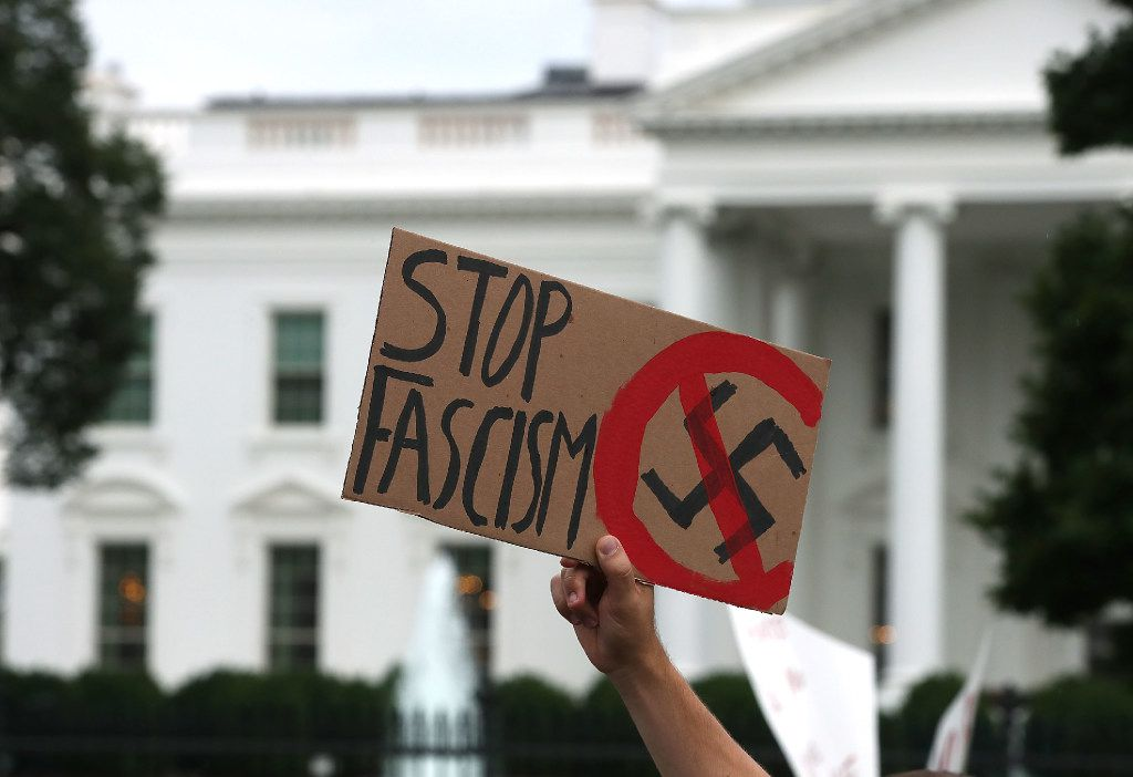 A man holds up a sign during a protest against racism gathered in front of the White House, on August 14, 2017 in Washington, DC. Today President Trump called out white nationalist groups by name following heavy criticism that his initial statement did not condemn racist groups that rallied in Charlottesville last weekend.