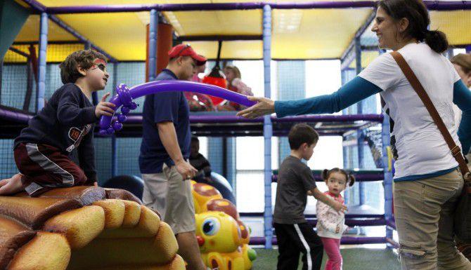 Christian Gatins, de tres años, juega con su madre Laura Gatins en el jardín de juegos en el centro recreacional de Lake Highlands.(BEN TORRES)