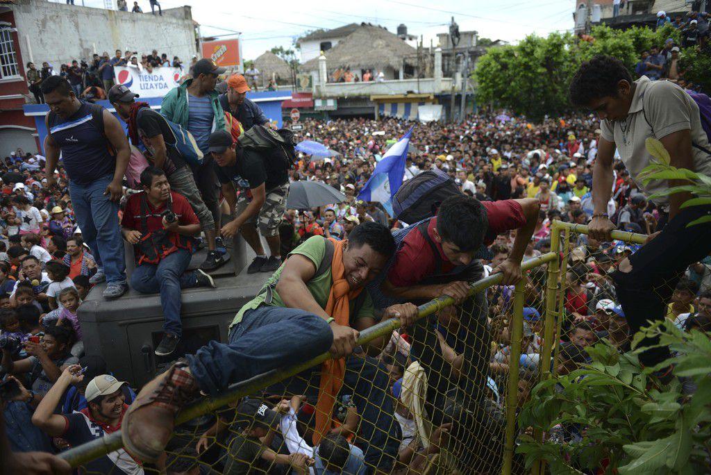 Miles de migrantes hondureños cruzan la frontera hacia México, en Tecun Uman, Guatemala, el jueves 18 de octubre de 2018. Los migrantes rompieron las puertas en el cruce de la frontera y comenzaron a correr hacia un puente hacia México (AP Photo/Oliver de Roos)