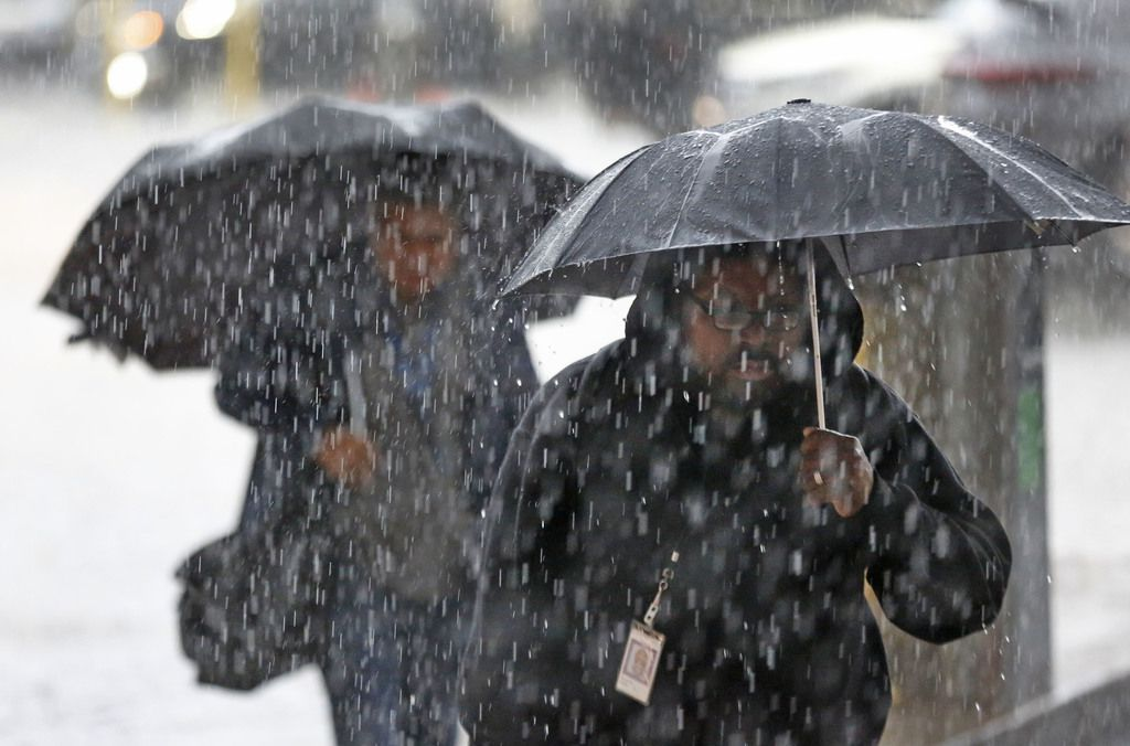 Pedestrians walk through a downpour as they arrive at the Earle Cabell federal courthouse, downtown Dallas, photographed on Wednesday, September 26, 2018. (Louis DeLuca/The Dallas Morning News)