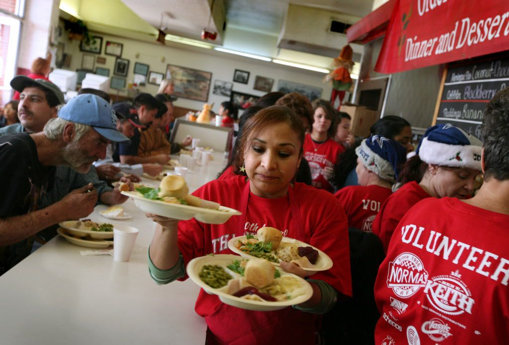 Volunteer Ana Barron, center, carries plates of free food to customers at Norma's Cafe in Oak Cliff on Thanksgiving Day Thursday November 27, 2008.