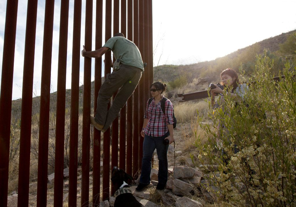 In this May 11, 2016, file photo, Tim Foley shows how to climb a section of the border wall separating Mexico and the United States near where it ends as journalists Chitose Nakagawa, right, and Marcie Mieko Kagawa look on in Sasabe, Ariz. Foley, a former construction foreman, founded Arizona Border Recon, a group of armed volunteers who dedicate themselves to border surveillance. With bids due Tuesday, April 4, 2017, on the first border wall design contracts, companies are preparing for the worst if they get the potentially lucrative but controversial job. (AP /Gregory Bull)