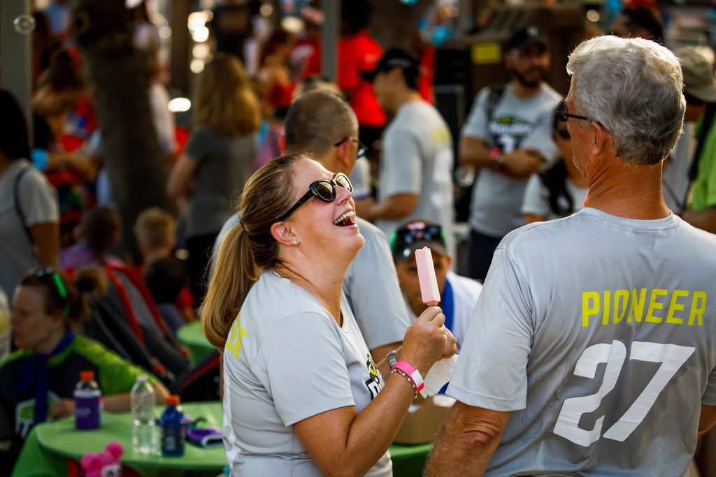 Pioneer Natural Resources team members Dennis Dronzek (right) and a smiling Shelly Ahlerich enjoy popsicles and camaraderie during opening ceremonies for annual Corporate Challenge in Richardson.