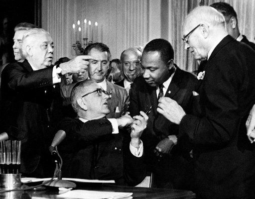 President Lyndon B. Johnson hands a pen to the civil rights leader the Rev. Martin Luther King after signing the historic Civil Rights Act in the East Room of the White House, in Washington, D.C., July 2, 964.