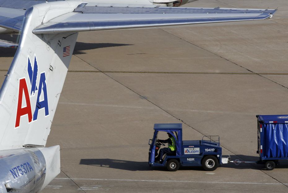 An employee drives with a baggage cart behind an American Airlines jet at DFW Airport.