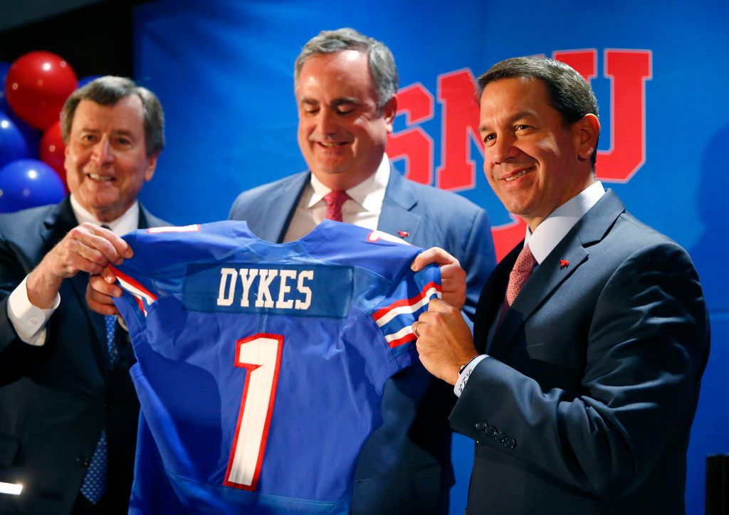 SMU president Gerald Turner (left) and athletic director Rick Hart (right) hand new SMU football coach Sonny Dykes his jersey at The Miller Event Center at SMU in Dallas on Dec. 12, 2017.  (Nathan Hunsinger/The Dallas Morning News) ORG XMIT: DMN1712121153012620