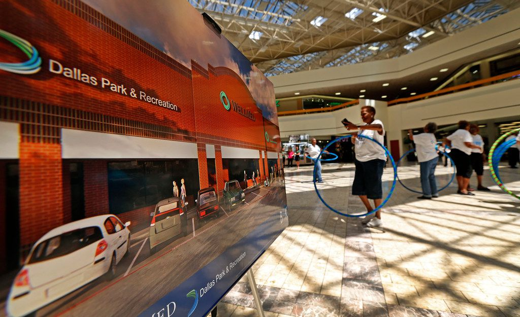 Seniors citizens participated in Chula hooping activity next to a rendering of the new health and wellness center during a news conference at Southwest Center Mall in Dallas in May.