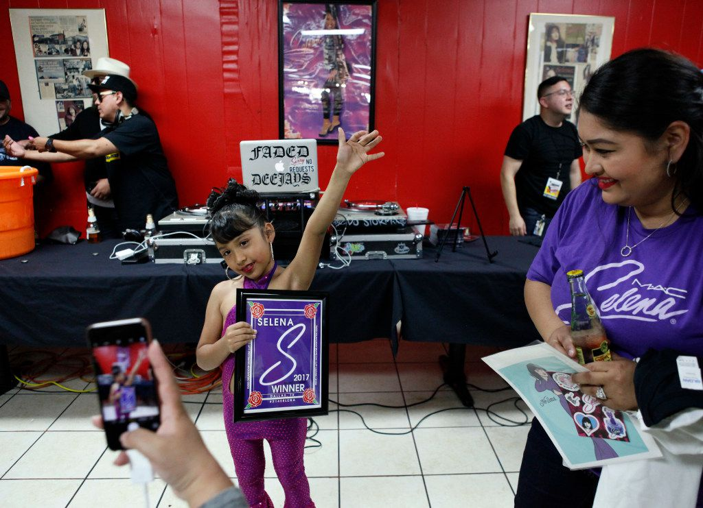 Monique Garcia (right) watches her daughter, Azlie Garcia, 6, raise her arm in victory after winning a Selena talent contest, during #214Selena.event last year.