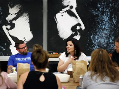 Senior director of communications Caitlin Van Wagoner (center) gives a gift to an outgoing member of the staff during a going-away lunch at Watermark Community Church in Dallas.