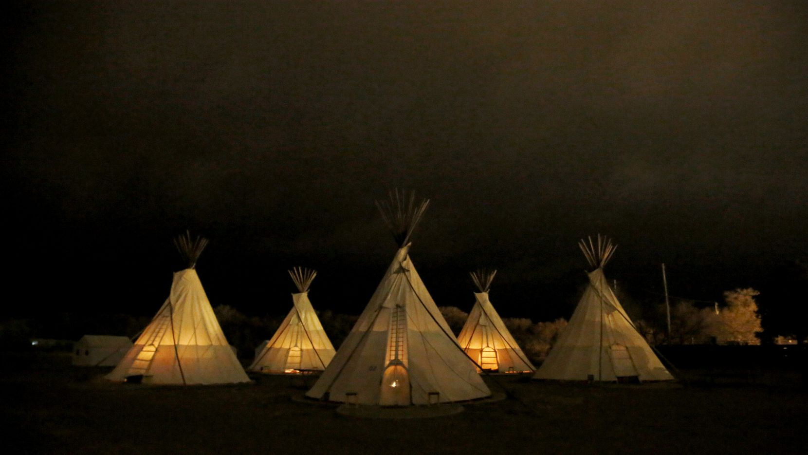 Teepees are illuminated by interior fire pits  before dawn at El Cosmico. (Guy Reynolds/Staff Photographer)