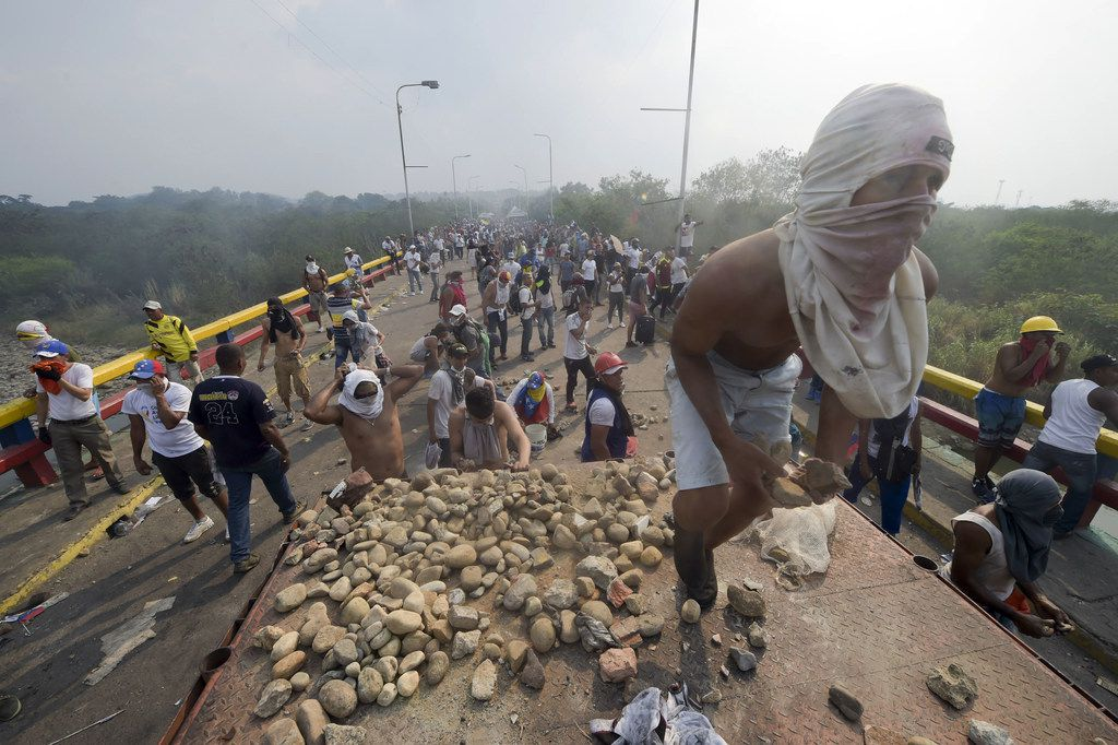"TOPSHOT - Demonstrators throw stones after a truck was set on fire at the Francisco de Paula Santander international bridge Bridge linking Cucuta, Colombia, and Urena, Venezuela, during an attempt to cross humanitarian aid over the border into Venezuela, on February 23, 2019. - US-donated humanitarian aid was ""on its way"" to Venezuela, opposition leader Juan Gauido announced Saturday as he launched a distribution operation with the presidents of Colombia, Chile and Paraguay."