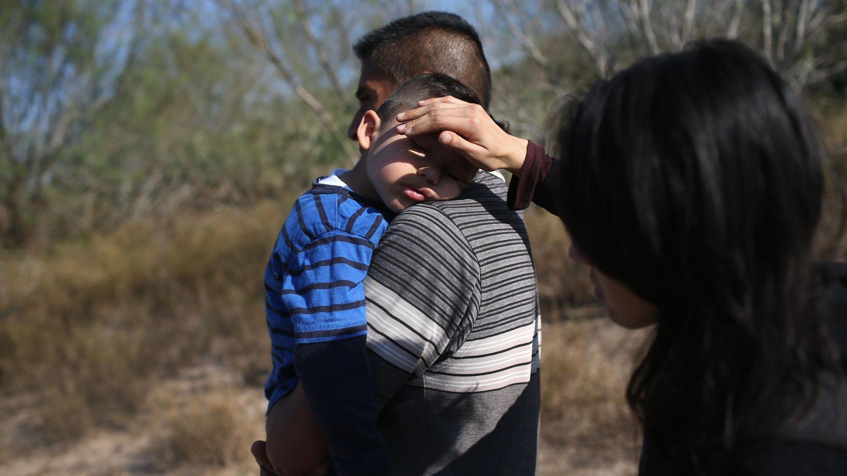 Una madre tapa el sol en la cara de su hijo luego de cruzar la frontera de México hacia Estados Unidos. Esta familia luego fue detenida por la Patrulla Fronteriza.(GETTY IMAGES)