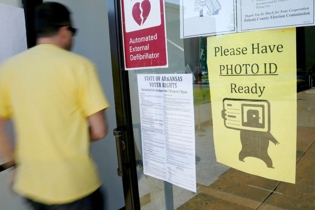 "A voter walks past a ""Please Have Photo ID Ready"" sign as he enters an early-voting polling place in downtown Little Rock, Ark. Arkansas' revived law requiring voters to show photo identification before casting a ballot will be put to the test when it takes effect this week. Voters heading to the polls early in three cities and two counties Tuesday, Aug. 1, 2017, for special elections on sales tax measures will be required to show photo ID before casting a ballot, or sign a sworn statement confirming their identity under the law approved by the Legislature earlier this year."