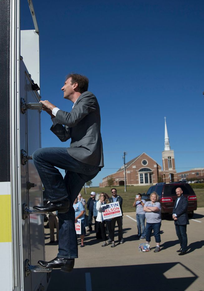 """Justin Nelson, who is attempting to unseat Texas Attorney General Ken Paxton, climbs a billboard truck before standing on top of it to deliver his campaign message during a rally at the Rockwall County Courthouse in Rockwall, Texas on Sunday, November 4, 2018. """"Truth is on our side,"""" Nelson said."""