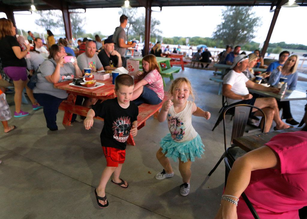 Jayden, left, and  Meike Sharpe dance to the tunes played by musician Joshua Irwin on the outdoor patio before the movies start at the Coyote Drive-In in Lewisville, Texas, photographed on Saturday, October 29, 2016. (Louis DeLuca/The Dallas Morning News)