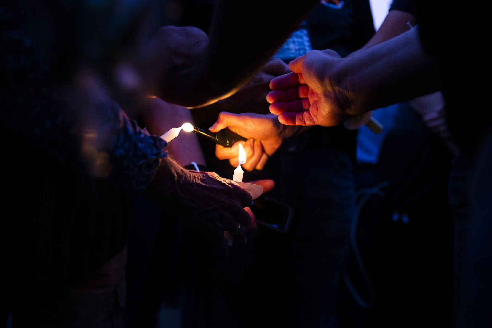 """Attendees try to light candles at a vigil Sunday at the Grand Prairie Public Safety Building for police Officer Albert """"A.J."""" Castaneda."""