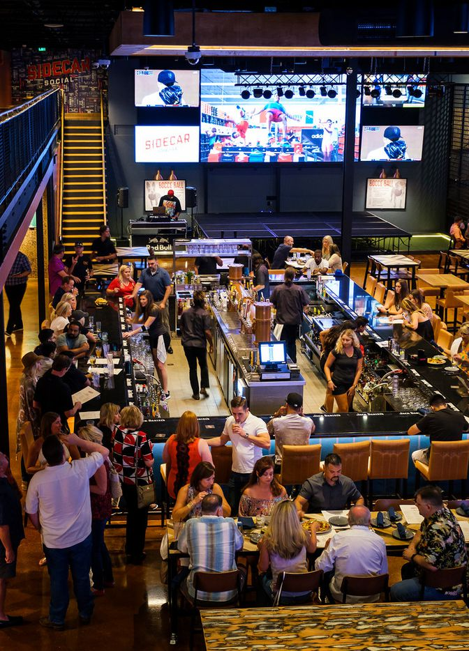 Large screen televisions surround a large bustling bar at Sidecar Social.