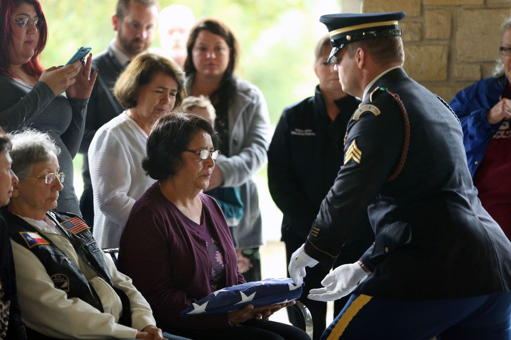 Lydia Bissell, wife of U.S. Army veteran Charles Bissell, receives a flag during a funeral for 10 veterans Friday at the Dallas-Fort Worth National Cemetery in Dallas.