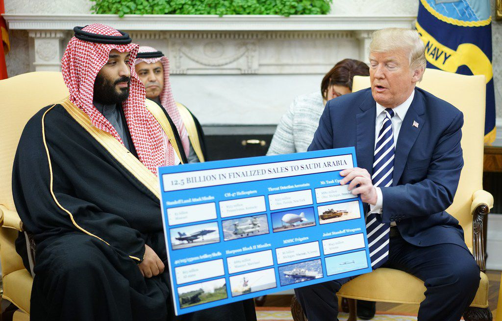 President Donald Trump holds a defense sales chart with Saudi Arabia's Crown Prince Mohammed bin Salman in the Oval Office of the White House in Washington, DC.