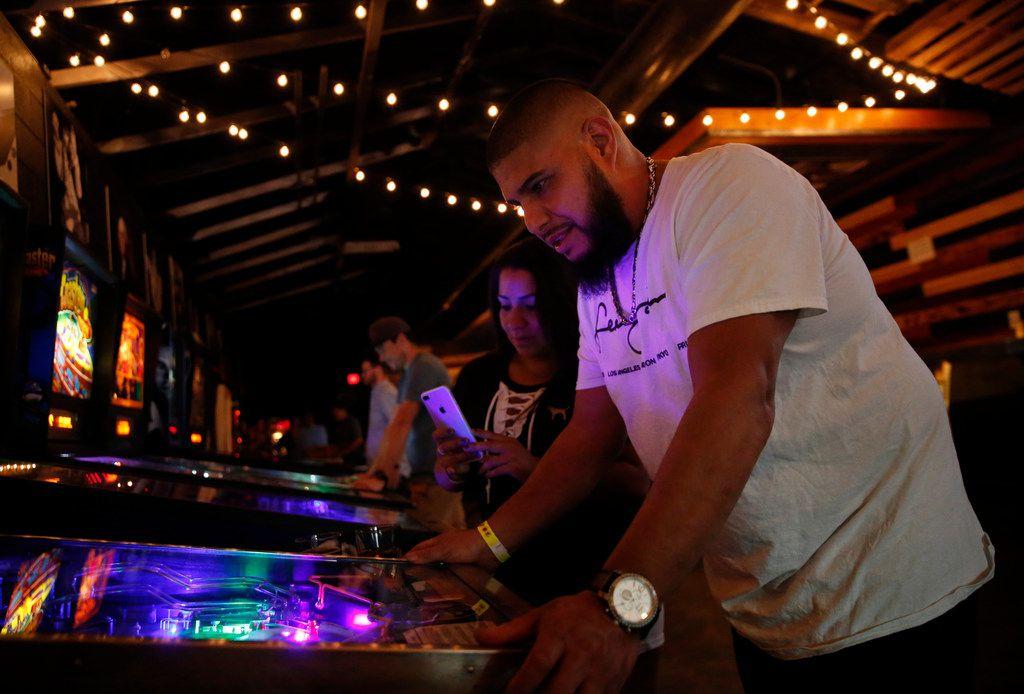 Juan Carranza plays pinball next to his wife Rebecca Carranza at Craftcade Pinball Bar in Fort Worth.