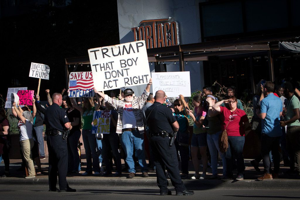 Protesters along Ross Avenue in Dallas as President Donald Trump's motorcade made its way through the city, Oct. 25, 2017. After a briefing on hurricane recovery efforts, Trump raised campaign funds at Belo Mansion. (Tom Brenner/The New York Times)