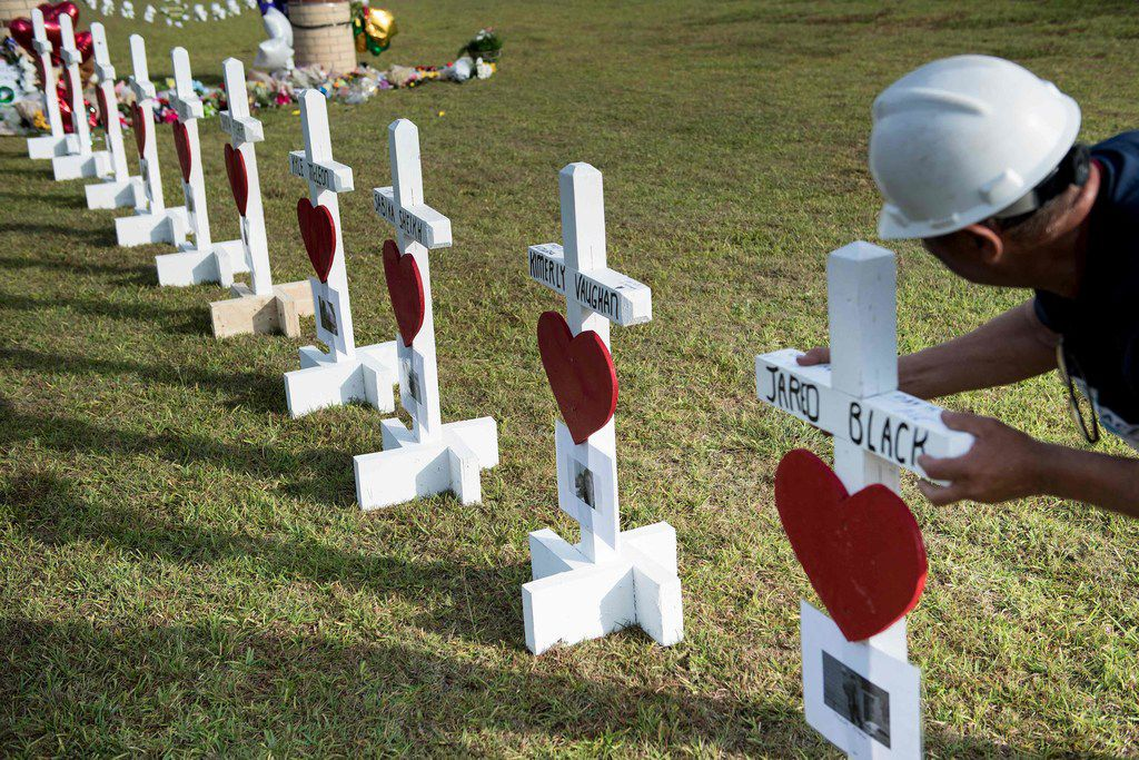 Greg Zanis lines up crosses for the victims of the Santa Fe High School shooting in front of the high school Monday.