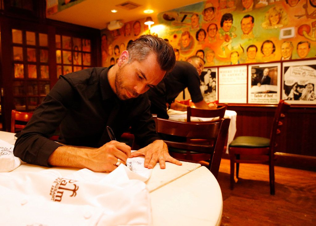 Eddie Maria signs coats after all the customers left on the last day of business at the Palm Restaurant in Dallas on Friday, June 30, 2017.