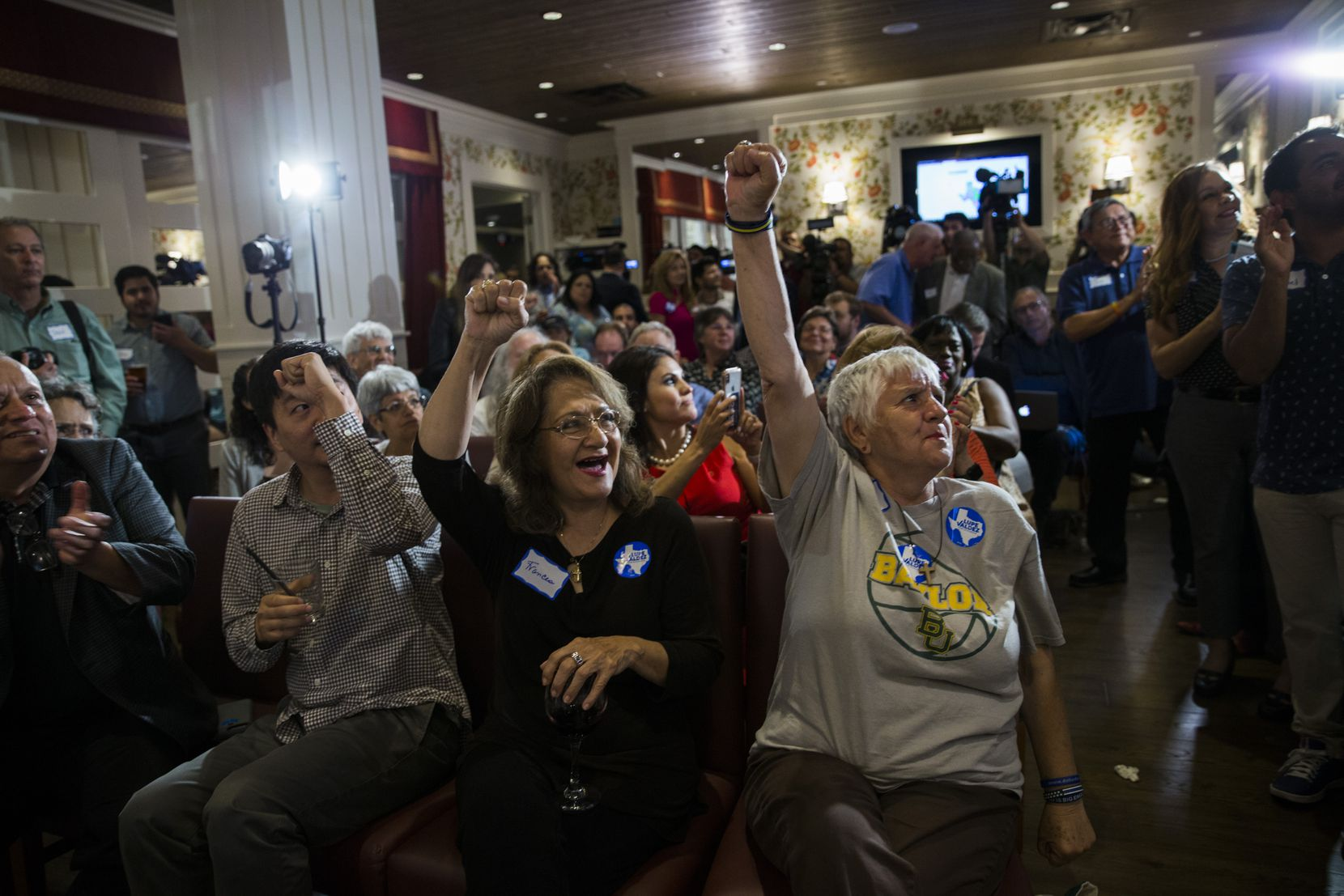 Frances Rizo, center, Sylvia Collins, right, and other supporters of gubernatorial candidate and former Dallas County Sheriff Lupe Valdez react to Valdez's win at Ellen's in Dallas on Tuesday, May 22, 2018.