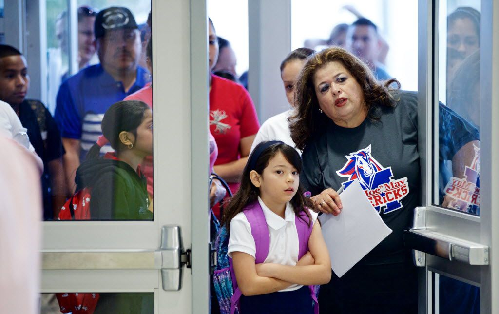 """Bilingual teacher's assistant Marta Gomez helped direct Merylinn Cabrera, 7, to her classroom on the first day of school at Jose """"Joe"""" May Elementary School in northwest Dallas on Monday."""