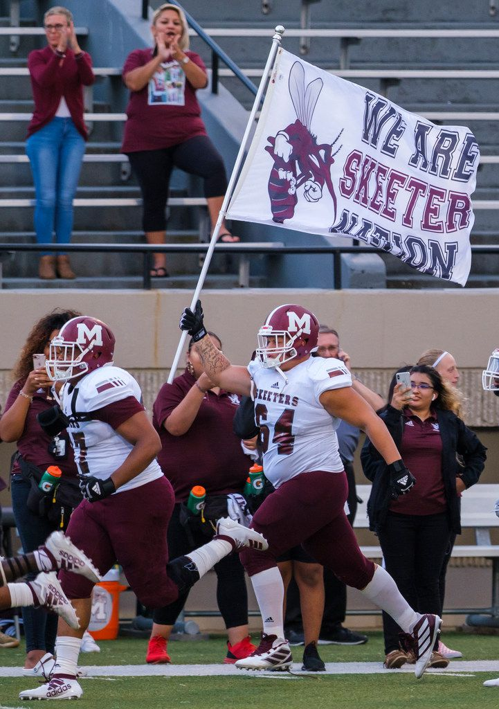 Mesquite offensive lineman J.D. Conley (64) carries the team flag as the Skeeters take the field for a high school football game against L.D. Bell on Thursday, Sept. 19, 2019, in Bedford, Texas. (Smiley N. Pool/The Dallas Morning News)